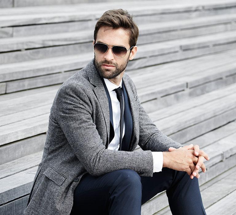 Szykownie ubrany mężczyzna siedzący naschodach